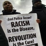 Woman holding Racism is the Disease Revolution is the Cure End Police Terror PSL sign