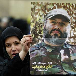 Woman in Beirut holds poster of Imad Mughniyah